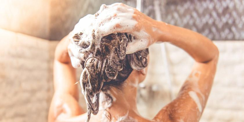 Woman washing her hair with shampoo.